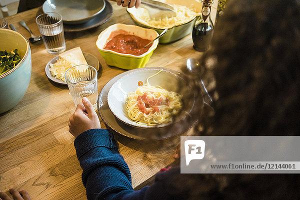 Mädchen essen Spaghetti mit Tomatensauce