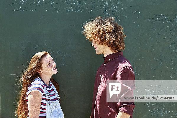 Lächelndes junges Paar vor einer grünen Wand