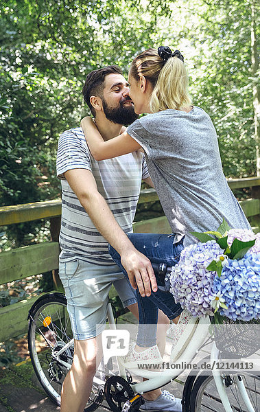 Couple with bicycle about to kiss on a wooden walkway in the countryside