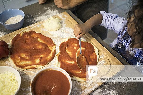Mädchen in der Küche lernt Pizza backen  Tomatensauce verteilen