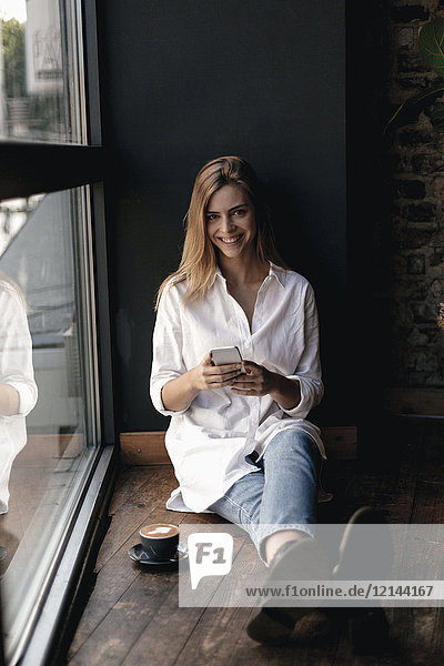 Young woman sitting on window sill in a cafe  using smartphone
