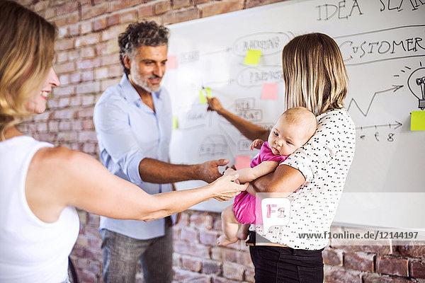 Kollegen streicheln Baby der berufstätigen Mutter im Büro