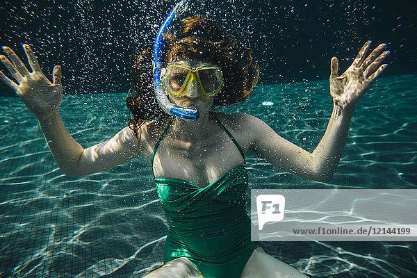 Porträt einer Frau mit Taucherbrille und Schnorchel unter Wasser im Schwimmbad
