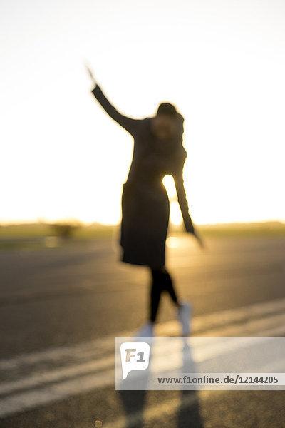 Verschwommener Blick auf eine Frau  die bei Sonnenuntergang auf einer Gasse läuft.