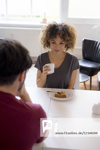 Smiling young woman eating cake at table looking at man