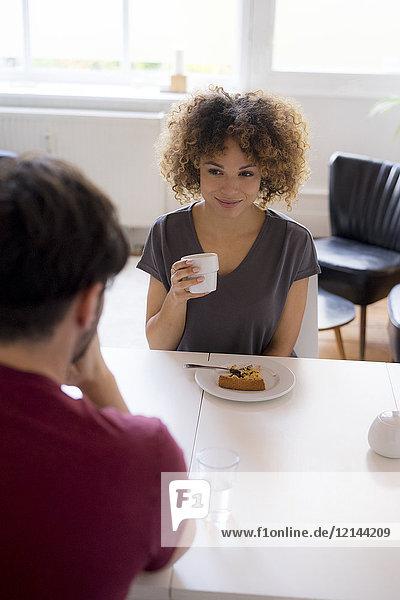Lächelnde junge Frau beim Kuchenessen am Tisch mit Blick auf den Mann