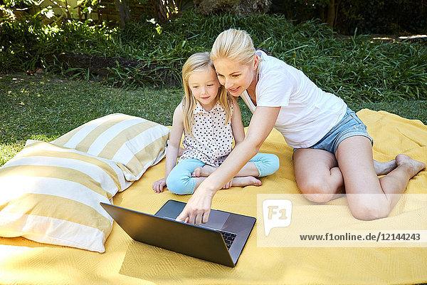 Mädchen und Mutter mit Laptop auf einer Decke