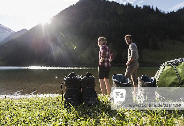 Österreich  Tirol  Wanderschuhe und Pärchen erfrischend im Bergsee