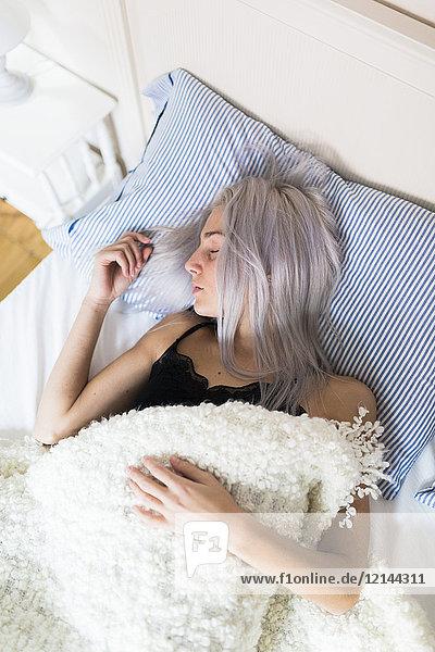 Junge Frau schläft im Bett