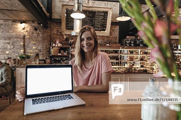 Junge Frau im Café sitzend  mit Laptop auf dem Tisch