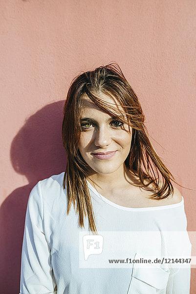 Porträt einer lächelnden jungen Frau  die sich an die Wand lehnt.