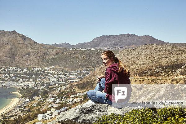 Südafrika  Kapstadt  junge Frau an der Küste sitzend mit Blick auf das Meer
