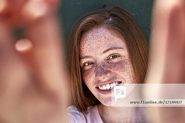 Porträt einer lächelnden jungen Frau mit Sommersprossen
