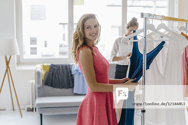 Smiling young woman choosing dress from clothes rail