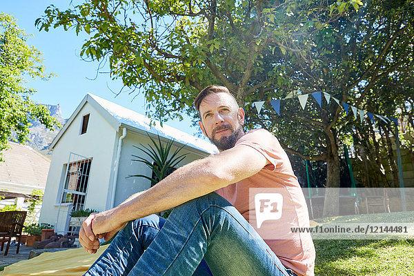 Porträt eines bärtigen Mannes  der vor einem Haus sitzt.