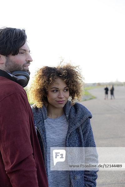 Lächelndes junges Paar steht draußen und schaut sich um.