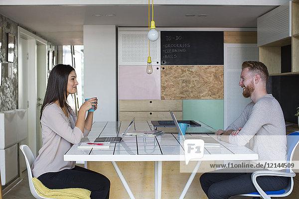 Lächelndes Paar mit zu Hause arbeitenden Laptops