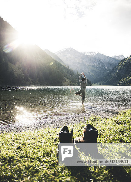 Austria  Tyrol  hiking shoes and man in yoga pose in mountain lake