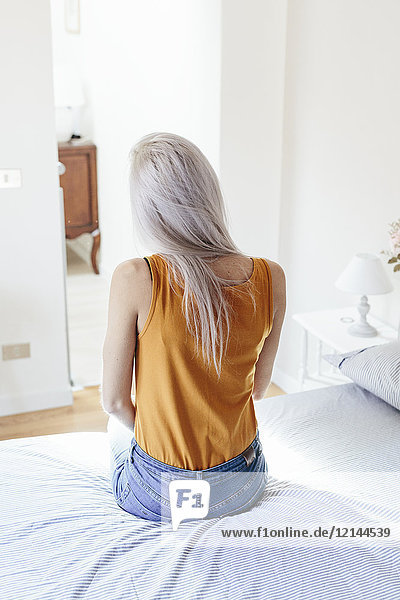 Rear view of young woman with long blond hair sitting on bed at home