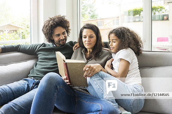 Glückliche Familie sitzend auf der Couch,  Lesebuch