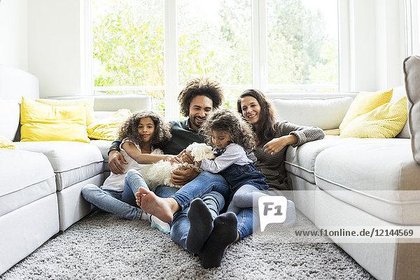 Fröhliche Familie mit Hund im gemütlichen Wohnzimmer