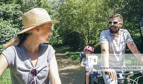 Couple talking while taking a family bike ride