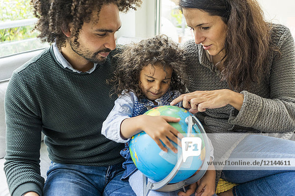 Glückliche Familie sitzend auf Couch mit Globus  Tochter lernt Geographie