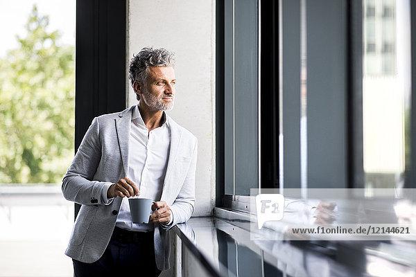 Lächelnder reifer Geschäftsmann mit Kaffeetasse aus dem Fenster schauend