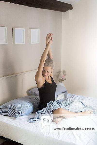 Junge Frau streckt sich im Bett