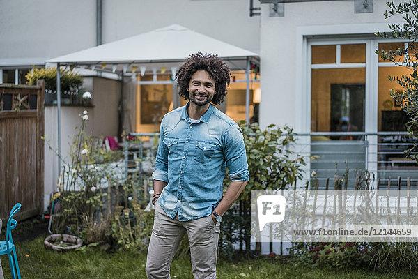 Glücklicher Mann steht in seinem Garten mit Händen in den Taschen.