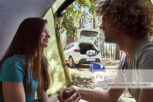 Lächelndes junges Paar im Zelt