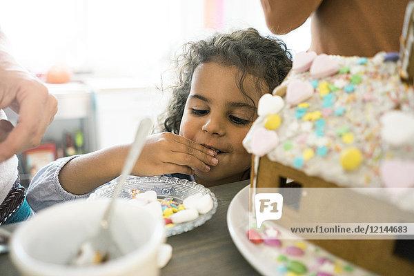 Kleines Mädchen knabbert Süßigkeiten für Weihnachten Lebkuchenhaus