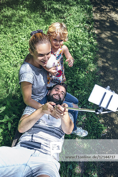 Happy man lying on a bench taking a selfie with his family