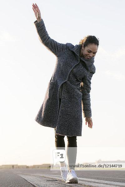 Fröhliche junge Frau  die auf einer Gasse läuft.