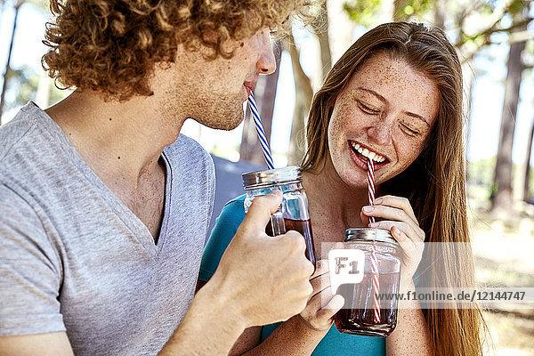 Glückliches junges Paar bei einem Drink im Wald