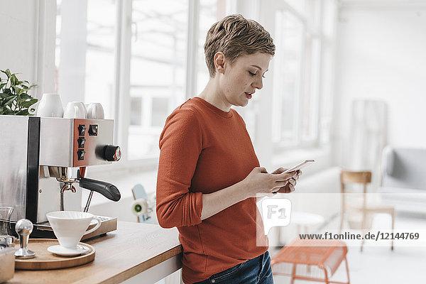 Frau mit Handy an der Kaffeemaschine