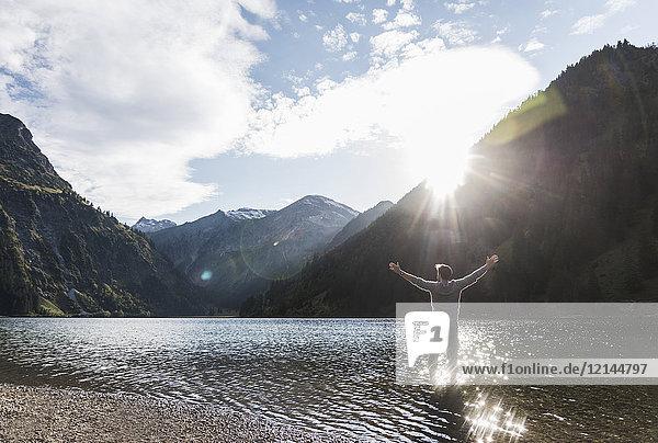 Österreich  Tirol  Wanderer stehend mit ausgestreckten Armen im Bergsee