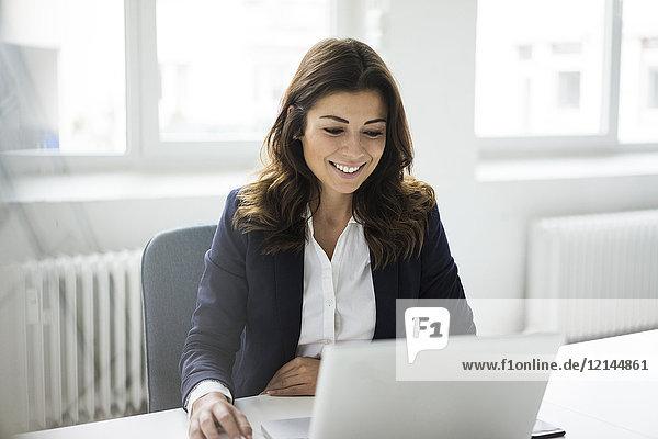 Porträt einer lächelnden Geschäftsfrau am Schreibtisch im Büro bei der Arbeit am Laptop