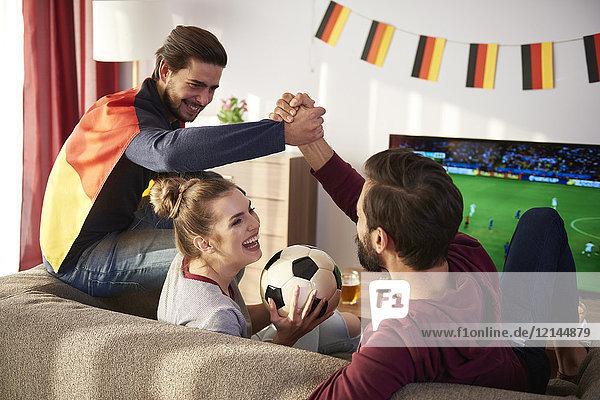 Deutsche Fußballfans beim Fernsehen und Jubeln