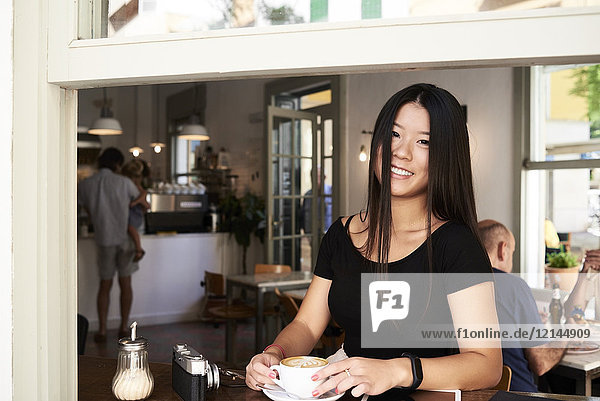 Fröhliche Asiatin in einem Café neben dem Fenster