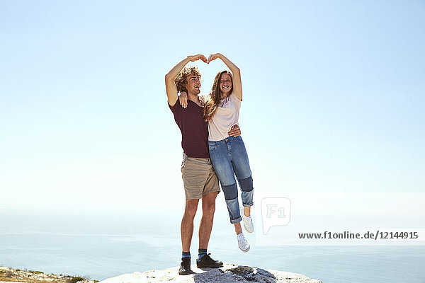 Südafrika  Kapstadt  glückliches junges Paar auf einem Berg an der Küste
