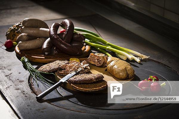 Leberwurst  Blutwurst  Frühlingszwiebel  Radieschen  Schnittlauch  Senf  Brot auf dem Schneidebrett  Kochplatte