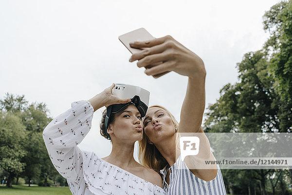 Zwei junge Frauen mit VR-Brille  die einen Selfie im Park mitnehmen.