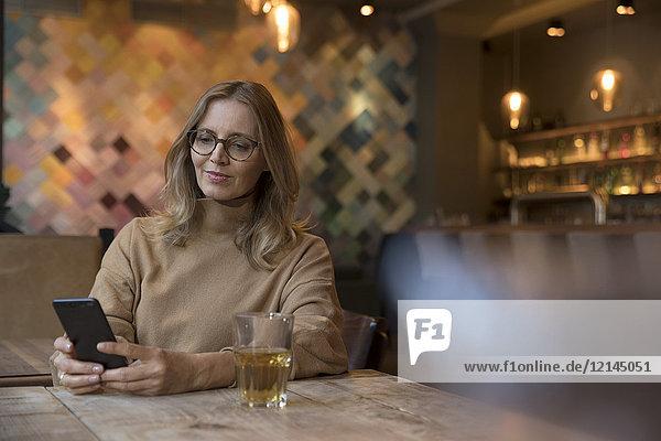 Portrait einer Geschäftsfrau im Restaurant mit Handy