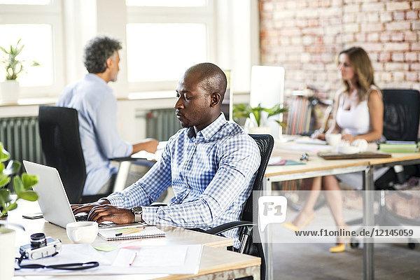 Geschäftsmann mit Laptop am Schreibtisch im Büro mit Kollegen im Hintergrund