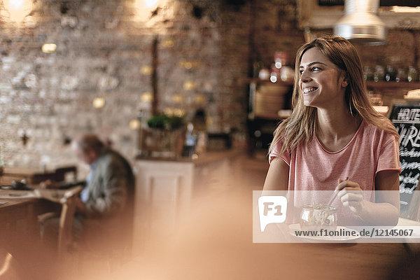Junge Frau sitzt im Café und isst Müsli zum Frühstück.