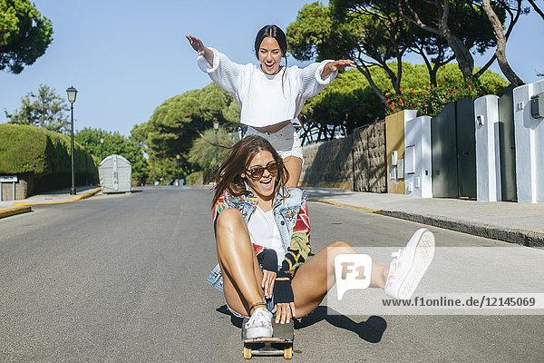 Zwei lachende Freunde zusammen auf dem Skateboard
