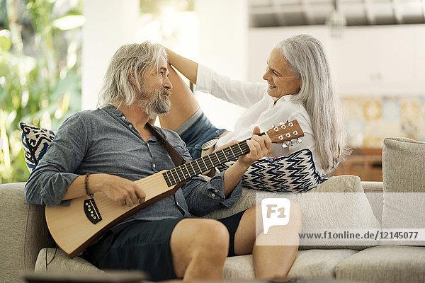 Senior Mann nimmt Selfie am Pool  während seine Frau Gitarre spielt.