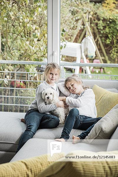 Portrait von zwei Mädchen mit Hund auf Couch im Wohnzimmer Portrait von zwei Mädchen mit Hund auf Couch im Wohnzimmer