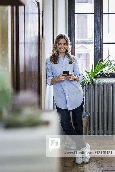 Porträt der lächelnden Frau mit Handy zu Hause